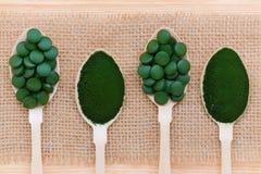 Gesunder Lebensstil, superfood, Meerespflanze, spirulina und Chlorellapillen und -pulver in den hölzernen Löffeln Stockfotos