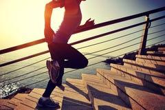 Gesunder Lebensstil trägt die Frau zur Schau, die oben auf Steintreppensonnenaufgang läuft Stockfoto