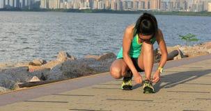 Gesunder Lebensstileignungs-Frauenläufer, der Spitze bevor dem Laufen auf sonniger Küste bindet stock footage