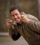 Hübscher, lächelnder Mann auf Schwingen Stockfoto