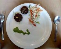 Gesunder Nahrungsmittelstarter und grüner Salat dienten in der weißen Platte mit Gabel und Löffel lizenzfreies stockfoto
