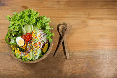 Gesunder Salat in der hölzernen Schüssel mit hölzerner Platte Stockbild
