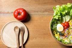 Gesunder Salat in der hölzernen Schüssel mit hölzerner Platte Stockfoto