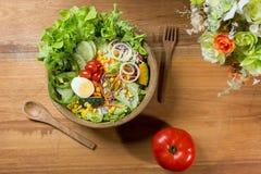 Gesunder Salat in der hölzernen Schüssel mit hölzerner Platte Lizenzfreies Stockfoto