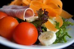 Gesunder Salat des Schinkens, der Tomaten, der Karotten, der Bananen, des usw. Auf einer weißen Platte Lizenzfreie Stockfotos
