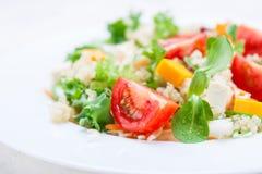 Gesunder Salat des selbst gemachten Herbstes mit Quinoa, Salatblättern, Tomaten, Kürbis und Feta auf einer weißen Platte Stockbild