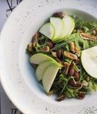 Gesunder Spinats- und Arugulasalat mit Koriander, getrockneten Feigen, gewürzten Mandeln und Apfel Stockfoto