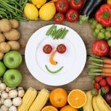Gesunder strenger Vegetarier, der lächelndes Gesicht vom Gemüse isst Lizenzfreie Stockbilder