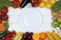 Gesunder Vegetarier, der Gemüse und Früchte auf leerer Platte isst Stockfoto