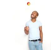 Gesunder werfender Apfel des jungen Mannes in der Luft lizenzfreies stockbild
