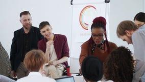 Gesundes Büro Glückliche junge lächelnde schwarze Geschäftsfrau, die aktive Diskussion mit verschiedenen Arbeitsplatzangestellten stock footage