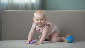 Gesundes Baby, das auf Sofa, spielend mit den bunten Spielwaren springt und genießen glückliches Leben stock footage