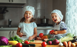 Gesundes Essen Glückliche Kinder bereitet Gemüsesalat im kitc zu lizenzfreies stockfoto