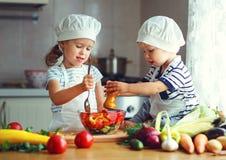 Gesundes Essen Glückliche Kinder bereitet Gemüsesalat im kitc zu stockbild
