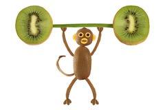 Gesundes Essen Lustiger kleiner Affe gemacht von der Kiwierhöhung das Ba Lizenzfreie Stockfotografie