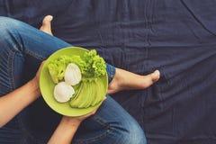 Gesundes Essenkonzept Frauen ` s übergibt Halteplatte mit Kopfsalat, Avocadoscheiben und poschierten Eiern Stockfotos