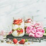Gesundes Frühlingsfrühstück rüttelt mit rosa raninkulus Blumen, quadratische Ernte lizenzfreie stockbilder