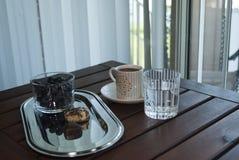 Gesundes Frühstück auf dem Balkon Tasse Kaffee, Plätzchen auf glänzender Platte, Glas reines Wasser und Blaubeeren auf Holztisch lizenzfreies stockbild