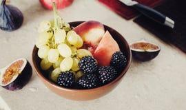 Gesundes Frühstück der Schüsselfrucht Traubenpfirsichbrombeerfeigen stockbild