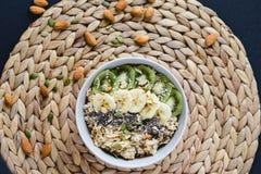 Gesundes Frühstück des strengen Vegetariers des Hafermehls mit Frucht auf einer Weidenserviette und einer Mandel stockbild