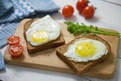 Gesundes Frühstück: durcheinandergemischte Eier auf Scheiben des Vollkornbrots mit Arugula und Tomaten auf einem hölzernen Brett Lizenzfreie Stockfotografie