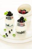 Gesundes Frühstück: Jogurt mit Erdbeere, Blaubeere und Brombeere verzierte tadellose Blätter auf weißem Holztisch Stockfotografie