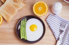 Gesundes Frühstück mit Spiegelei, Toast und Orange auf Tabelle Lizenzfreie Stockbilder