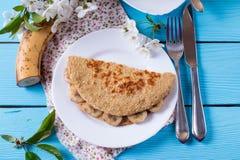 Gesundes Frühstück - Pfannkuchen vom Hafermehl mit Banane und Käse auf einem hölzernen Hintergrund Stockfoto