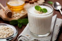Gesundes Frühstück von Bananensmoothie oder -milchshaken mit Hafern und Honig verzierte tadellose Blätter Stockfotografie