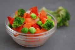 Gesundes Gemüse des gefrorenen bunten strengen Vegetariers Brocolli, Karotten, Erbsen, Pfeffer Vertikales Bild Grauer Hintergrund stockfoto