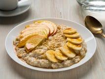 Gesundes Hafermehl des Frühstücks morgens - mit Frucht und Honig, Scheiben von Äpfeln und Bananen, Karamelsirup Lizenzfreie Stockfotografie