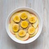 Gesundes Hafermehl des Frühstücks morgens - mit Frucht und Honig, Scheiben von Äpfeln und Bananen, Karamelsirup Stockbilder