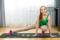 Gesundes junges lächelndes Mädchen, während auf Yogamatte trainieren Sie Stockfotografie