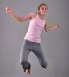 Gesundes junges muskulöses Jugendlichespringseil im Studio Kind, das mit auf grauen Hintergrund hoch springen trainiert Lizenzfreies Stockfoto