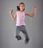 Gesundes junges muskulöses Jugendlichespringseil im Studio Kind, das mit auf grauen Hintergrund hoch springen trainiert Stockbilder
