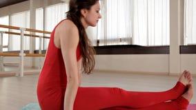 Gesundes junges schönes Mädchen in der roten Klage, welche die Übung sitzt auf dem Teppich auf dem Boden im Raum mit Tageslicht t stock video footage