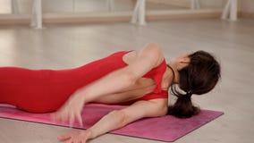 Gesundes junges schönes Mädchen in einer roten Klage, welche die Übung sitzt auf dem Teppich auf dem Boden in der Halle tut Das K stock video footage