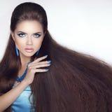Gesundes langes Haar Schönes Brunettemädchen Purpurrotes Make-up und bunte helle Nägel Fashi Stockfotos