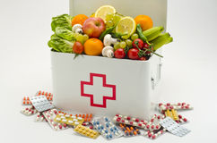 Gesundes Lebensmittel gegen medizinische Pillen Stockfotografie