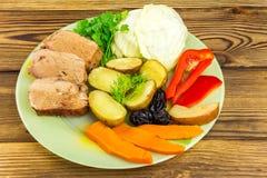 Gesundes Lebensmittel, geschnittenes Schweinefleisch mit gedämpftem verschiedenem Gemüse in der Platte auf hölzernem Hintergrund Lizenzfreie Stockfotos