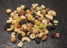 Gesundes Lebensmittel; Haselnüsse, Mandeln, Acajoubaum, Rosine und Trockenfrüchte auf einem schwarzen Steinhintergrund Lizenzfreies Stockfoto