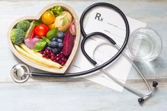 Gesundes Lebensmittel im Herzstethoskop und in der medizinischen Verordnungsdiät und im Medizinkonzept stockbilder