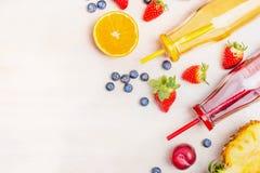 Gesundes Lebensmittel mit den roten und gelben Smoothies in den Flaschen mit Strohen und Bestandteilen: Orange, Erdbeere, Ananas, Lizenzfreie Stockfotos