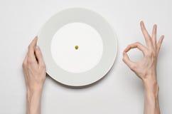 Gesundes Lebensmittelthema: Hände, die Messer und Gabel auf einer Platte mit grünen Erbsen auf einer weißen Tischplatteansicht ha Lizenzfreie Stockbilder
