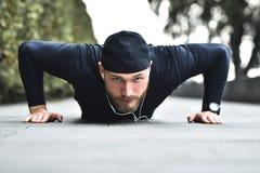 Gesundes Lebensstilkonzept Das muskulöse Athletentrainieren drücken sich oben draußen Stadtpark ein lizenzfreie stockfotografie
