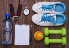 Gesundes Lebensstilkonzept Dummkopf, Expanderhand und Ball auf rustikalem Holztisch stockfoto