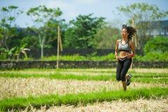 Gesundes Lebensstilporträt der jungen glücklichen und geeigneten asiatischen chinesischen Läuferfrau in laufendem Training drauße stockbilder