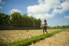 Gesundes Lebensstilporträt der jungen glücklichen und geeigneten südostasiatischen thailändischen Läuferfrau in laufendem Trainin lizenzfreie stockfotografie