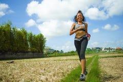 Gesundes Lebensstilporträt der jungen glücklichen und geeigneten südostasiatischen thailändischen Läuferfrau in laufendem Trainin stockbild