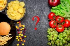 Gesundes Nahrungkonzept Obst und Gemüse gegen ungesundes Fa Lizenzfreie Stockfotografie